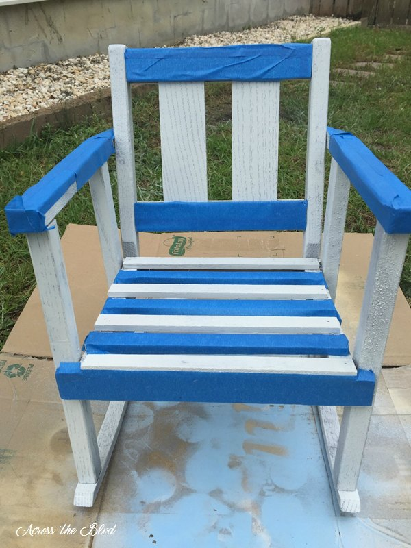 small rocking chair painted white and painter's tape