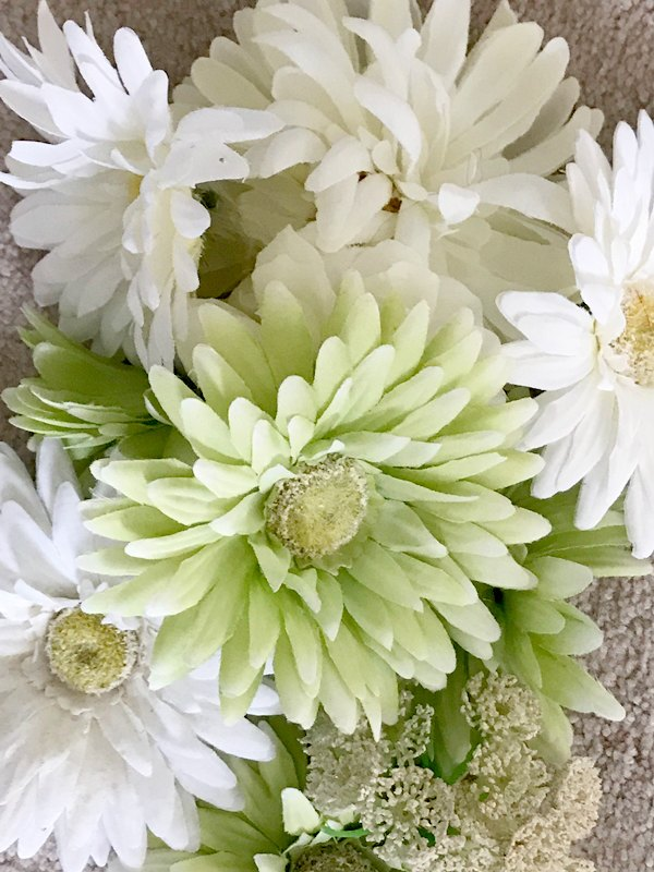 faux daisy blooms for leprechaun hat centerpiece