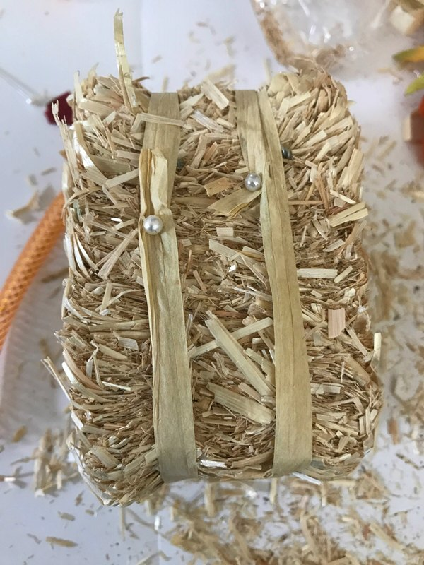 Mini hay bale wrapped with strips of raffia