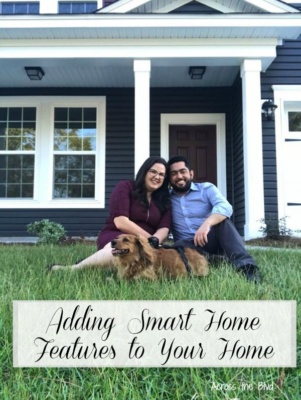 Couple and dog sitting on lawn in front of new home Ways to Add Smart Home Features to Your Home