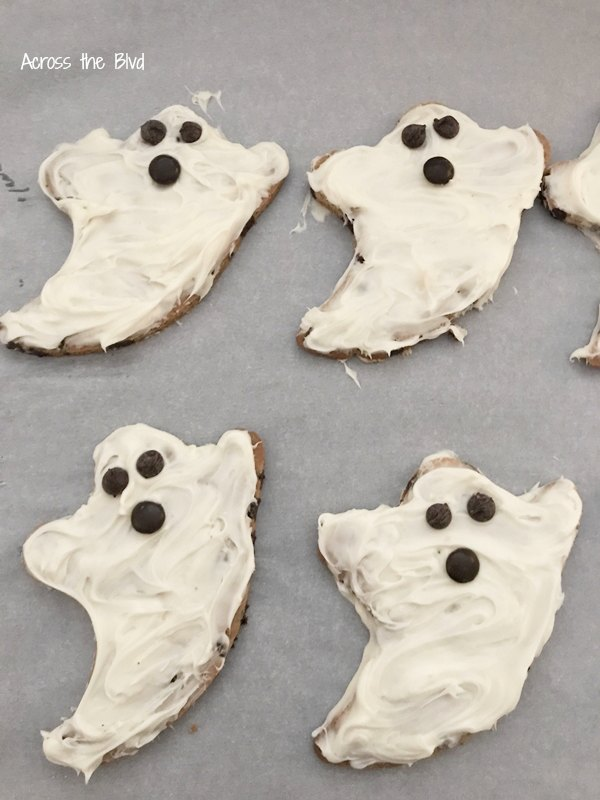 Easy Halloween Ghost Cookies with candy eyes and mouth