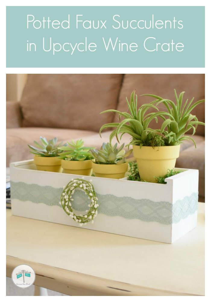Faux succulents in yellow pots in white wood crate