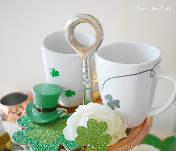 white mugs with vinyl shamrocks in gray and green sitting on a tiered copper tray