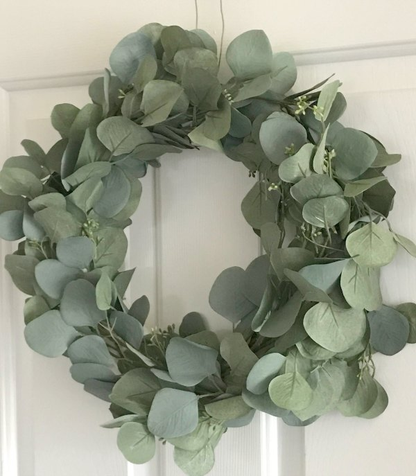 faux eucalyptus wreath on white door