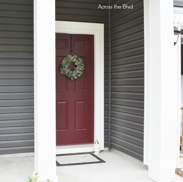 burgundy front door on gray house with eucalyptus wreath
