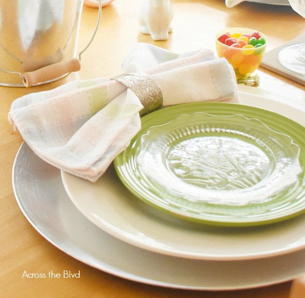 Place setting with silver chargers white plates and green salad plates and multi-colored napkins
