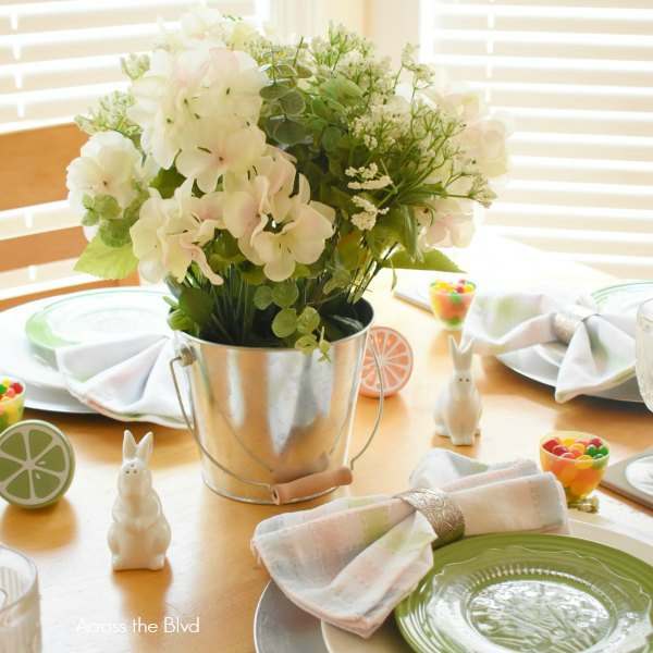 Easter Table Setting with Green Plates and White Flowers in Metal Pail
