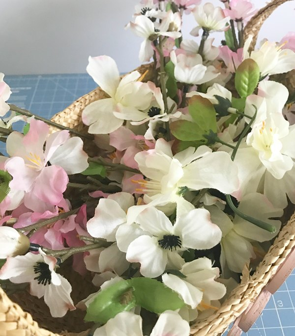 basket of faux pink and white small flowers
