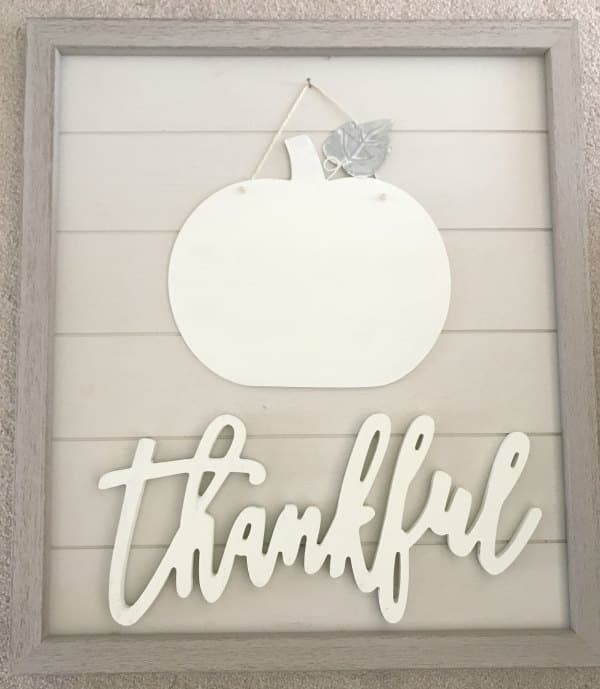 white pumpkin and thankful wood sign on large shiplap frame