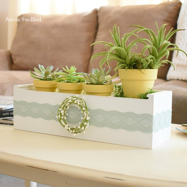 faux succulents in white wood crate