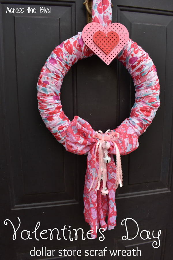 Valentine's Day wreath made using scarves hanging on black door