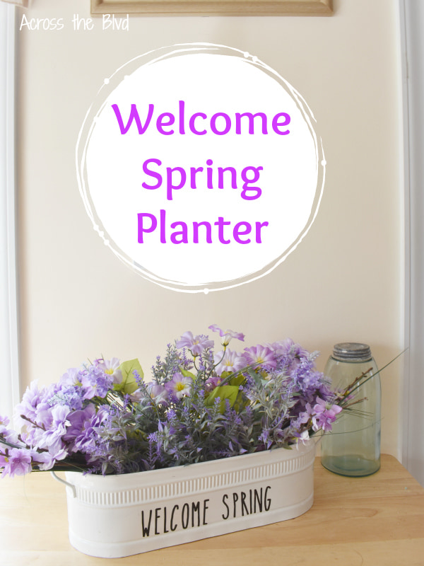 white metal planter with faux purple flowers