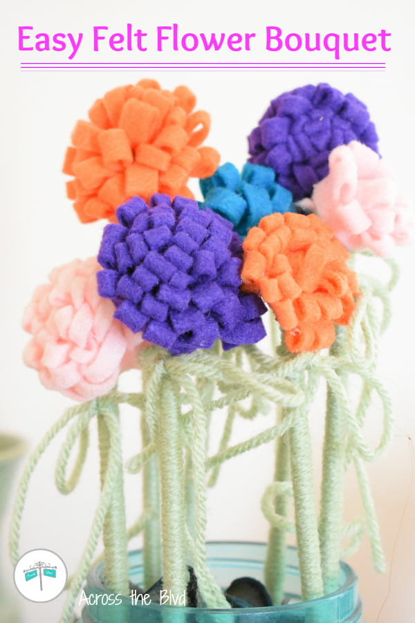 assorted colors of felt flowers with green yarn wrapped stems in aqua jar.