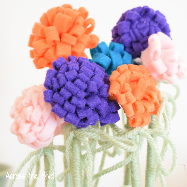assortment of colors of diy felt flowers on yarn wrapped stems.