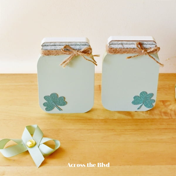 two mason jar shapes painted light green with a shamrock on corner