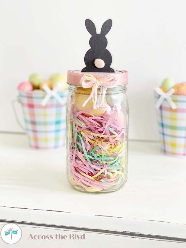 mason jar with colorful Easter grass, eggs and topped with a bunny